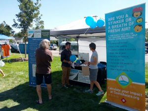 Booth at festival with balloons, banners about the NFRMPO and air quality, and three people